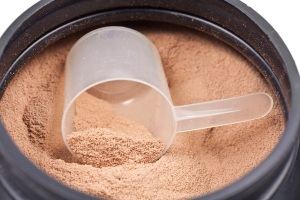 Scoop of chocolate whey isolate protein in black plastic contain